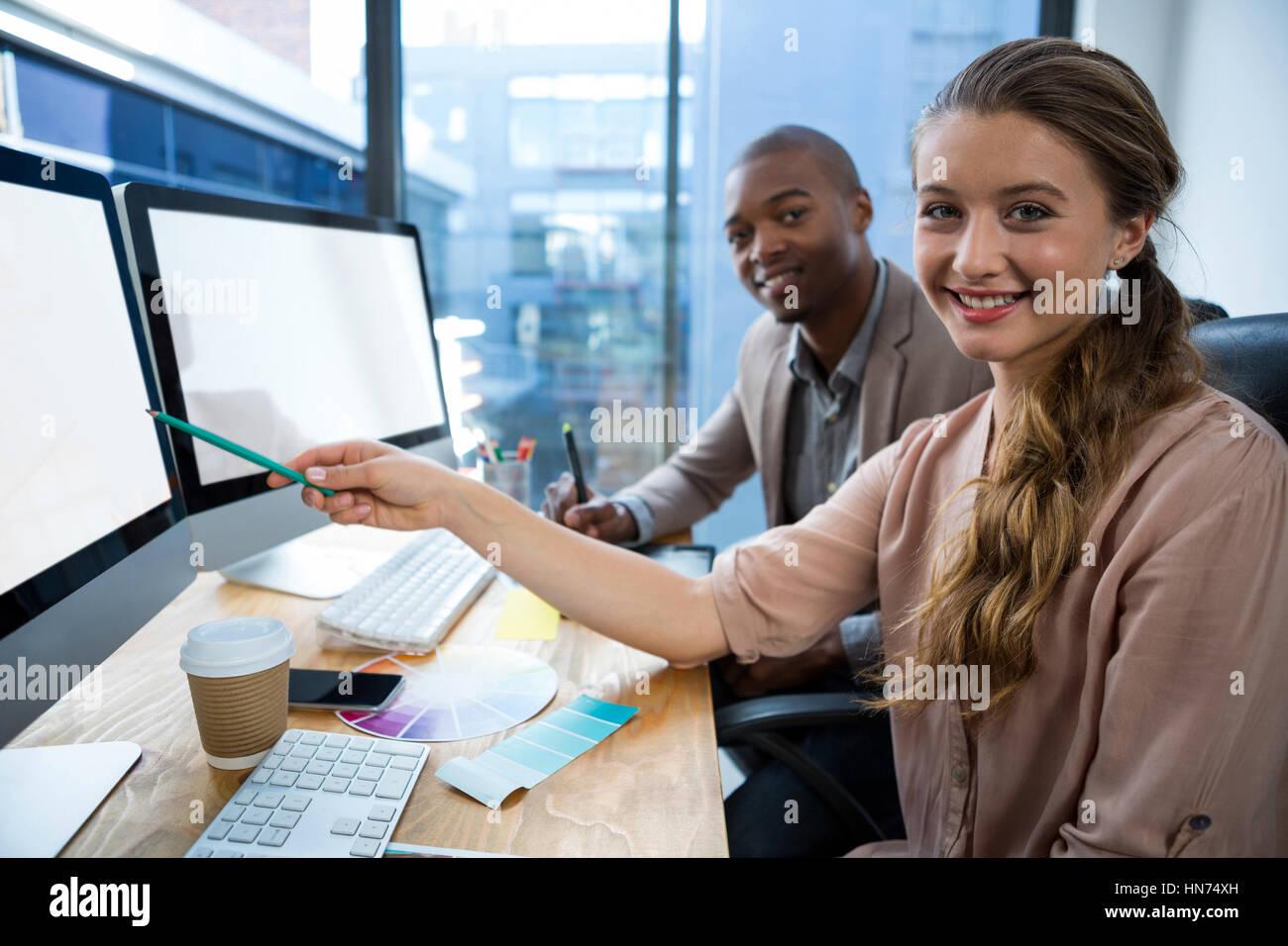 Porträt von Grafik-Designer Schreibtisch mit Kollegen im Büro Stockbild
