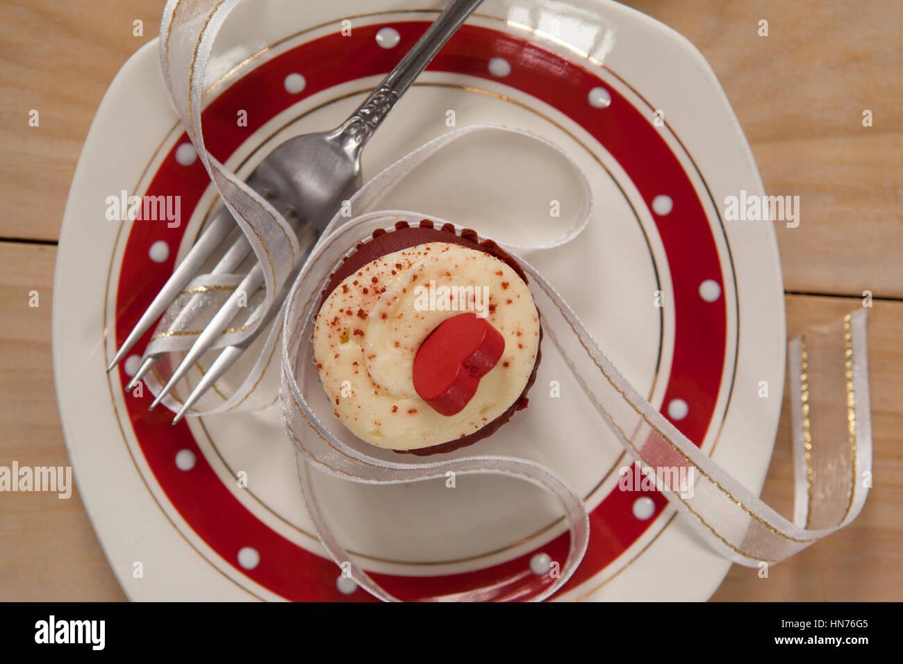 Teller mit leckeren Cupcake verziert mit einer Schleife auf Holztisch Stockbild