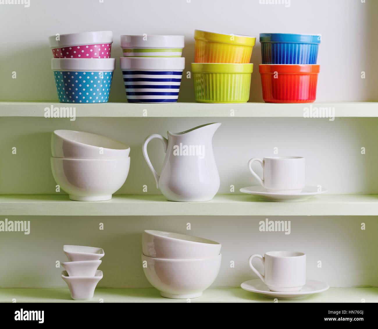 Vielfalt der Keramik im Regal. Bunte Schüsseln, Tassen und weißem Geschirr. Stockbild