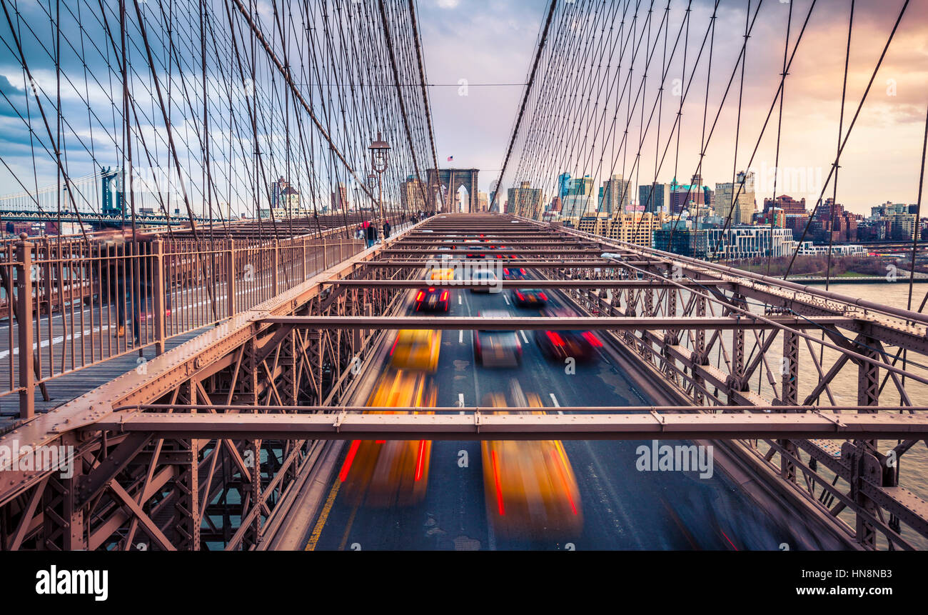 Verkehr auf Brooklyn Bridgeat bewölkten Sonnenuntergang in New York City Stockfoto