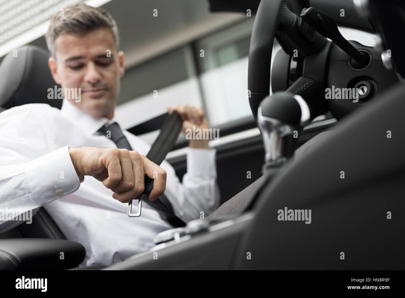 Geschäftsmann in seinem Auto Befestigung Sicherheitsgurt, sichere treibende Konzept Stockbild