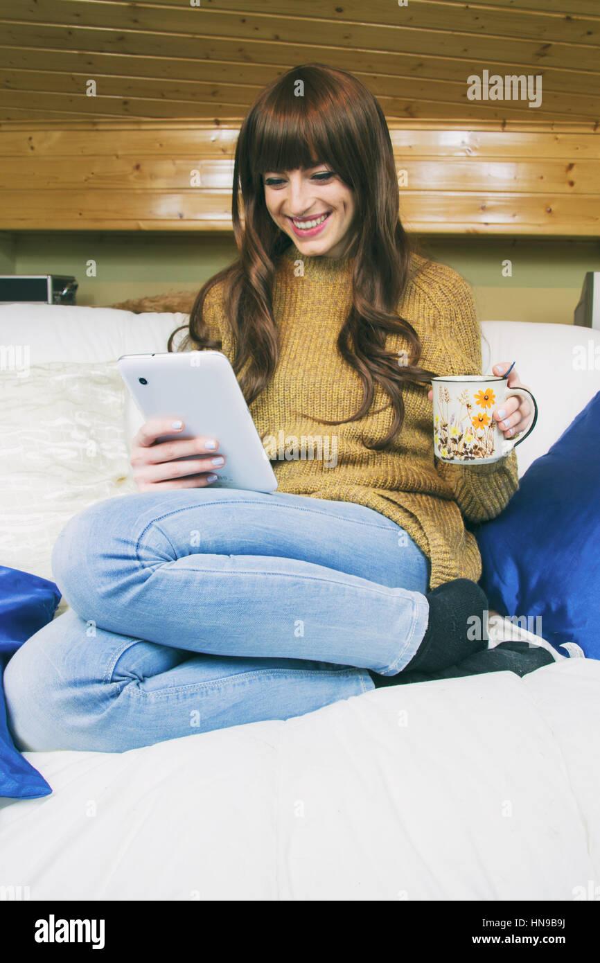 Junge Frau mit ihrem Tablet und einer Tasse Kaffee Stockbild