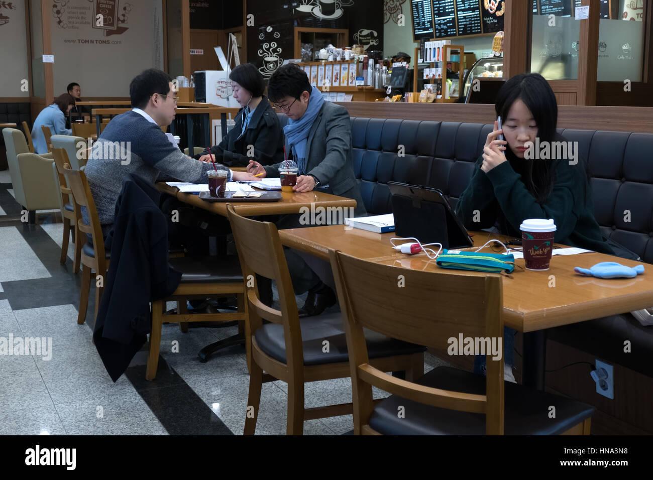 Jungen koreanischen Studenten studieren mit Handy und Tablet Ipad, asiatische Menschen arbeiten in einer Cafeteria, Stockfoto