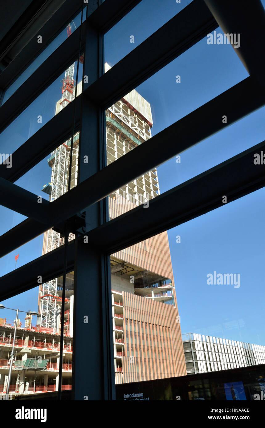 Bürohochhaus im Bau durch die Fenster eines anderen Gebäudes gesehen. Stockbild