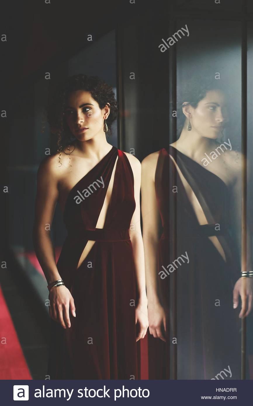 Elegante junge Frau in einem roten Kleid Stockbild