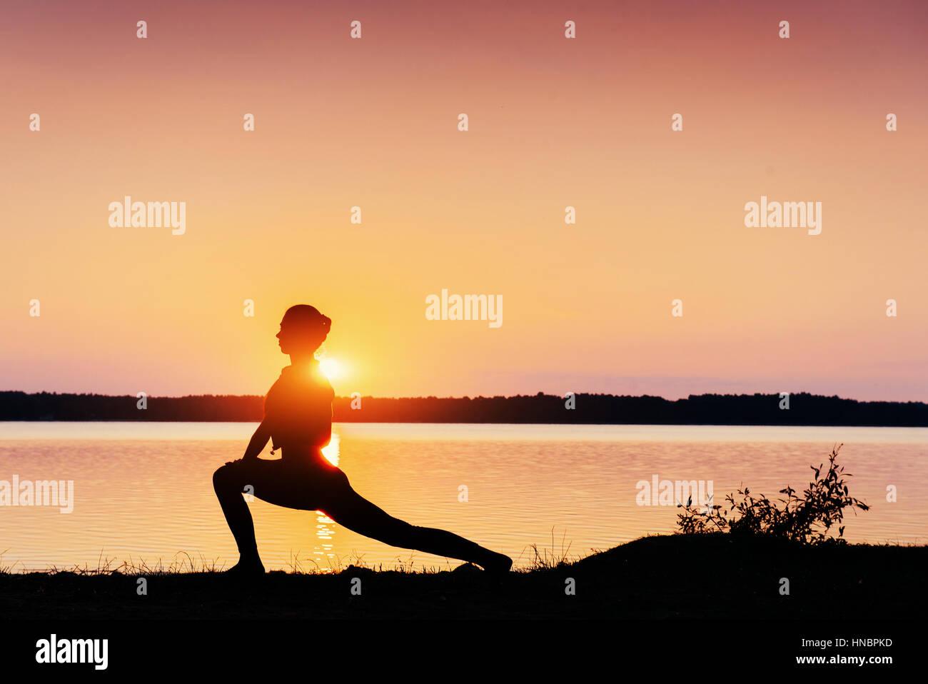 Mädchen bei Sonnenuntergang am See Stockbild