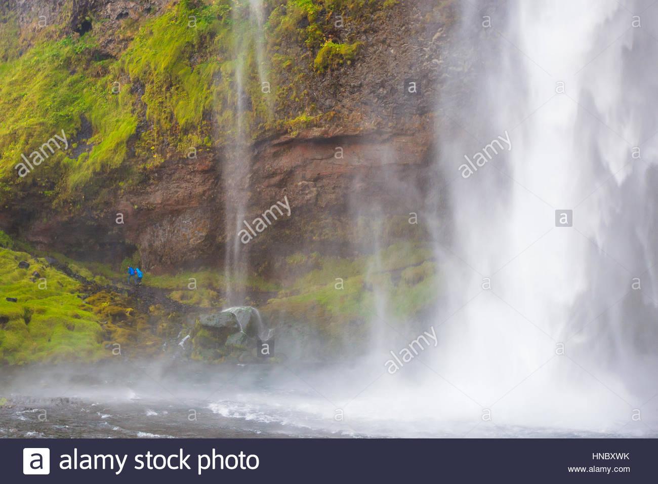 Touristen in die landschaftlich reizvolle und beliebte Seljalandsfoss Wasserfälle. Stockbild
