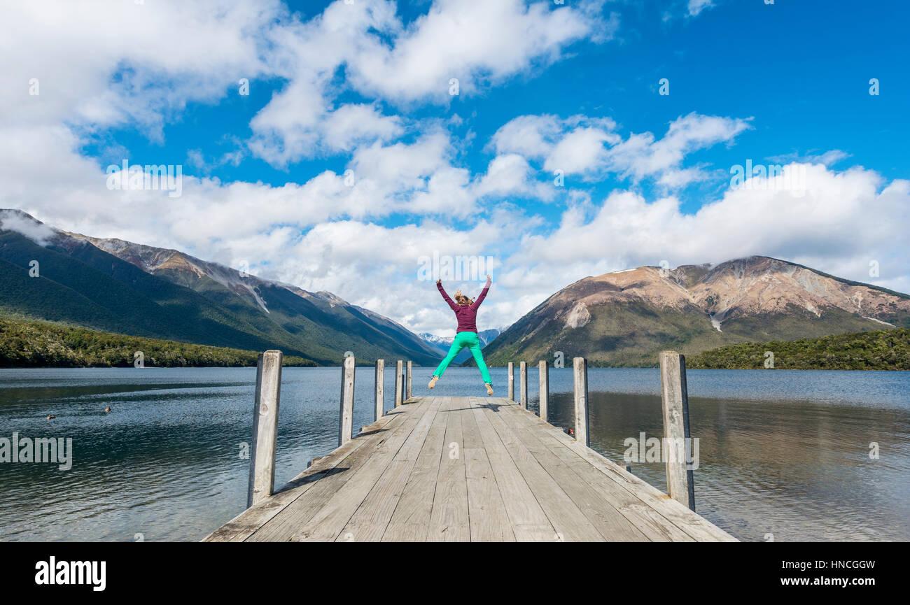 Frau in die Luft springen dock am Lake Rotoiti, Nelson Lakes National Park, Tasman District, Southland, Neuseeland Stockbild