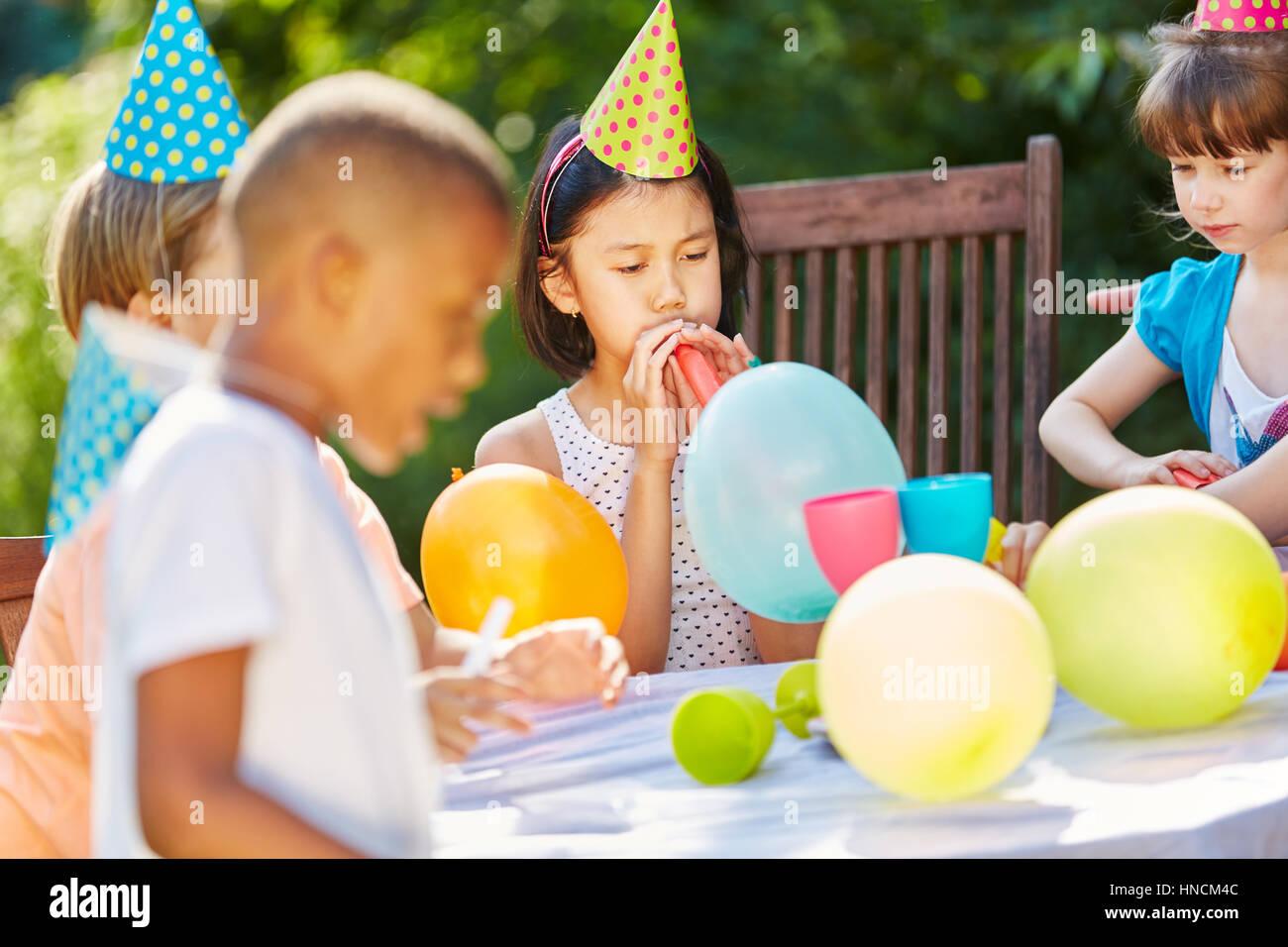 Kinder feiern mit bunten Luftballons und Hüte auf Geburtstagsparty im Garten Stockbild