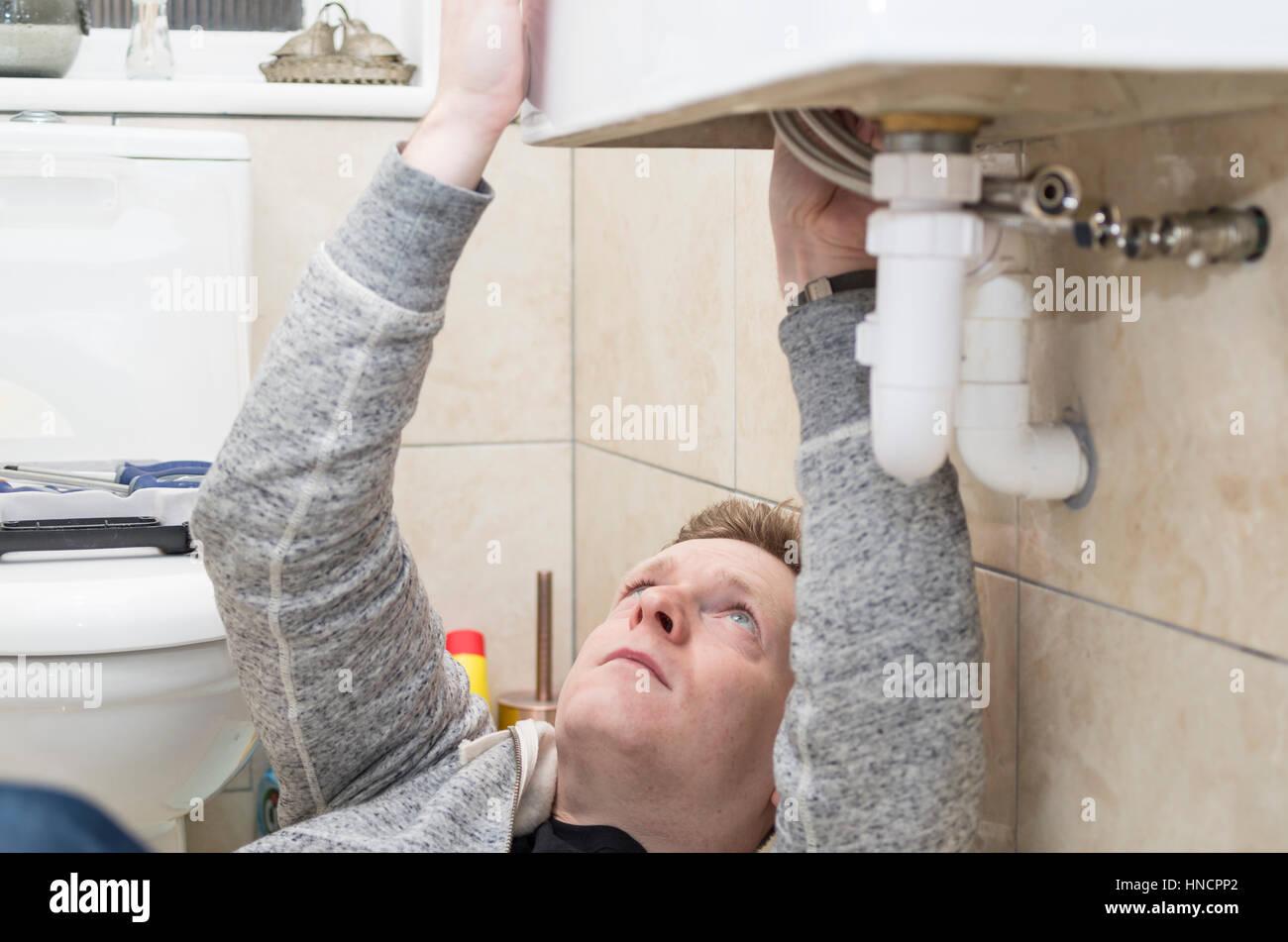 Superb Junger Mann Tun Es Yourself (DIY) Versucht Zu Hause Unter Einer Spüle  Montage Einen Neuen Wasserhahn Sanitär.