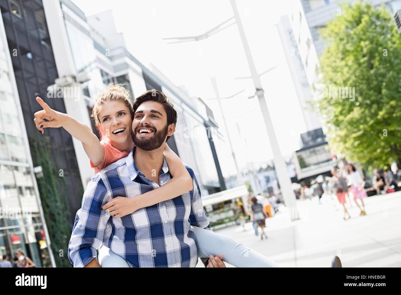Glückliche Frau zeigen etwas zu Mann und genießen Huckepack Fahrt in die Stadt Stockbild