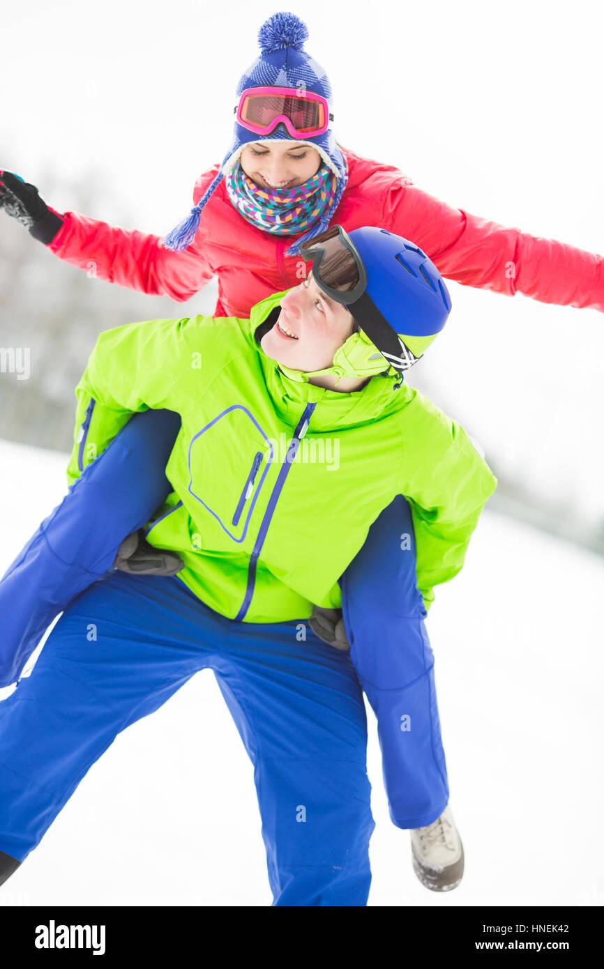 Glücklich Jüngling geben Huckepack Fahrt zur Frau im Schnee Stockfoto