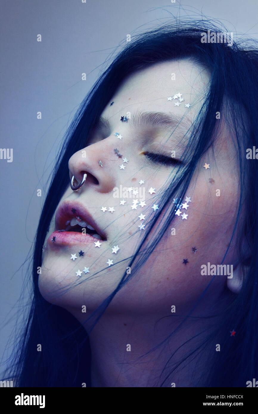 Künstlerische Porträt einer Frau mit ihrem Gesicht abdecken mit vielen silbernen Sternen Stockbild