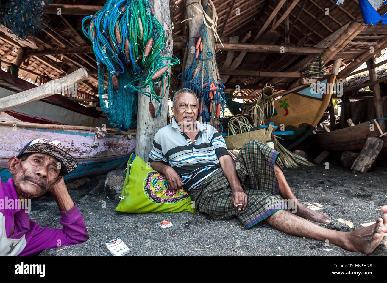 Zwei Männer vor einer Holzhütte entspannen fungierte als Abstellraum für traditionelle Boote und Stockbild