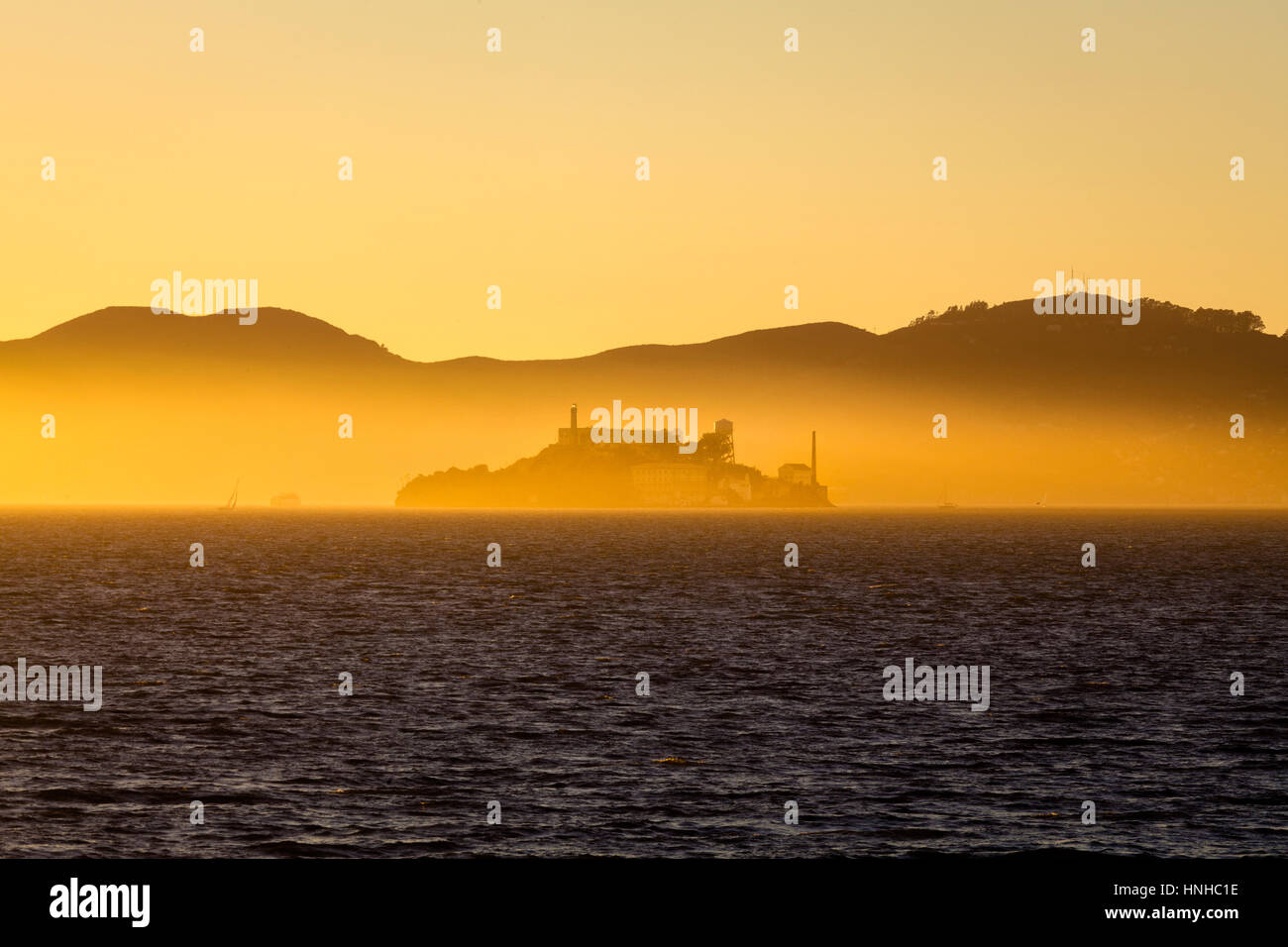 Schöne Aussicht auf die berühmte Insel Alcatraz beleuchtet im majestätischen goldenen Abendlicht Stockbild