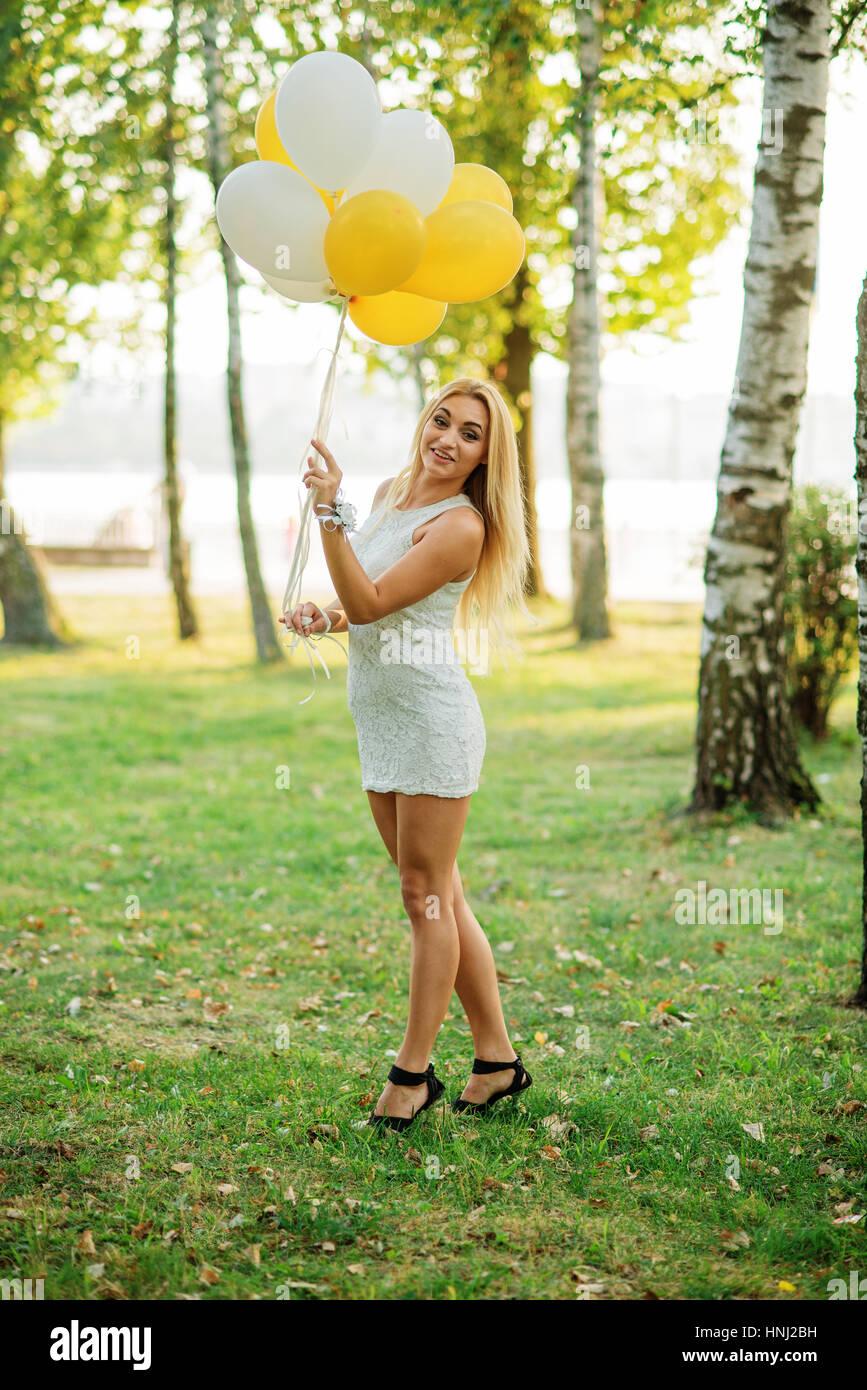 Porträt von blonden Mädchen tragen weiße Kleid mit Luftballons auf ...