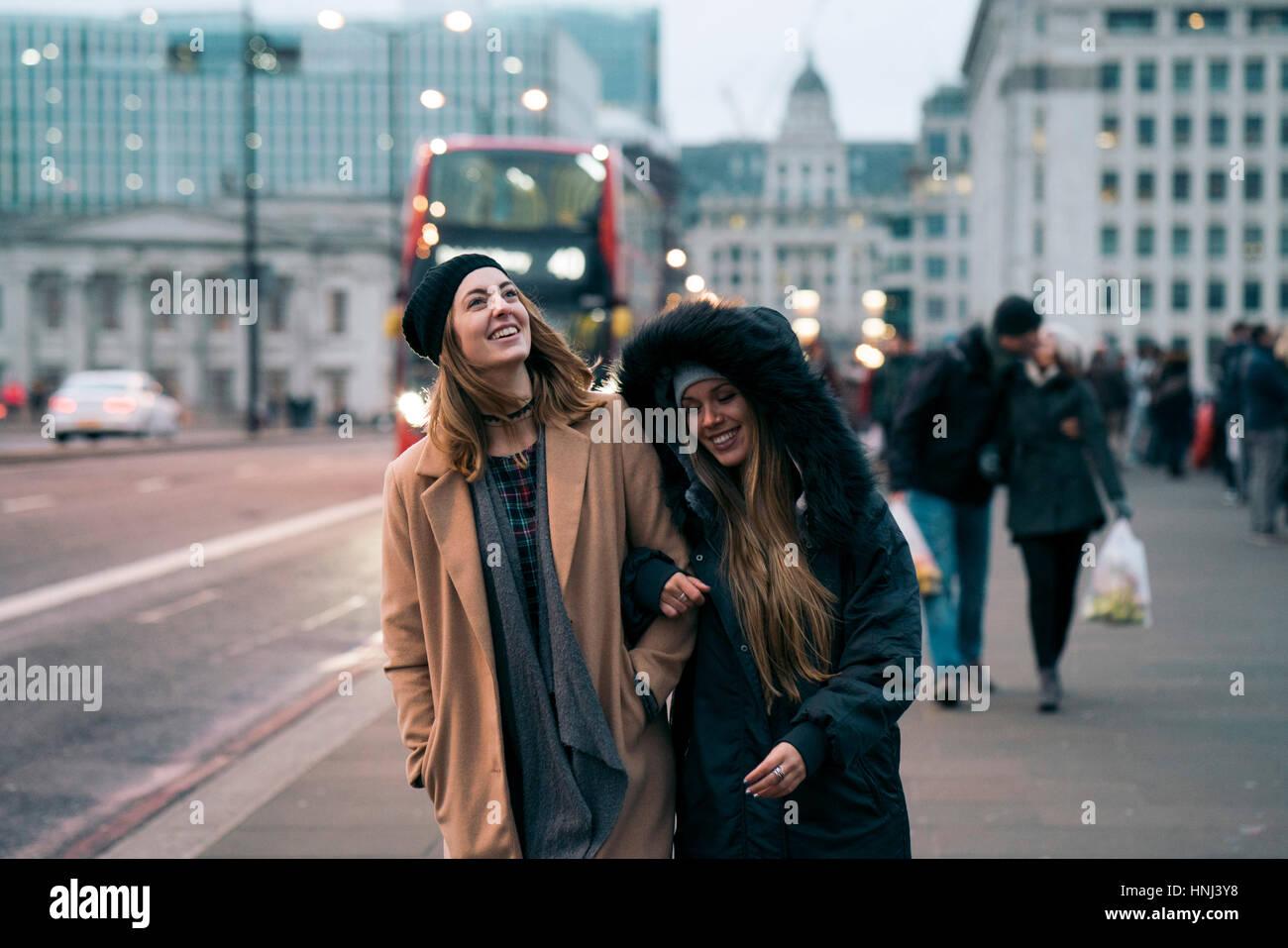 Lächelnden Freunde zu Fuß unterwegs in der Stadt Stockbild
