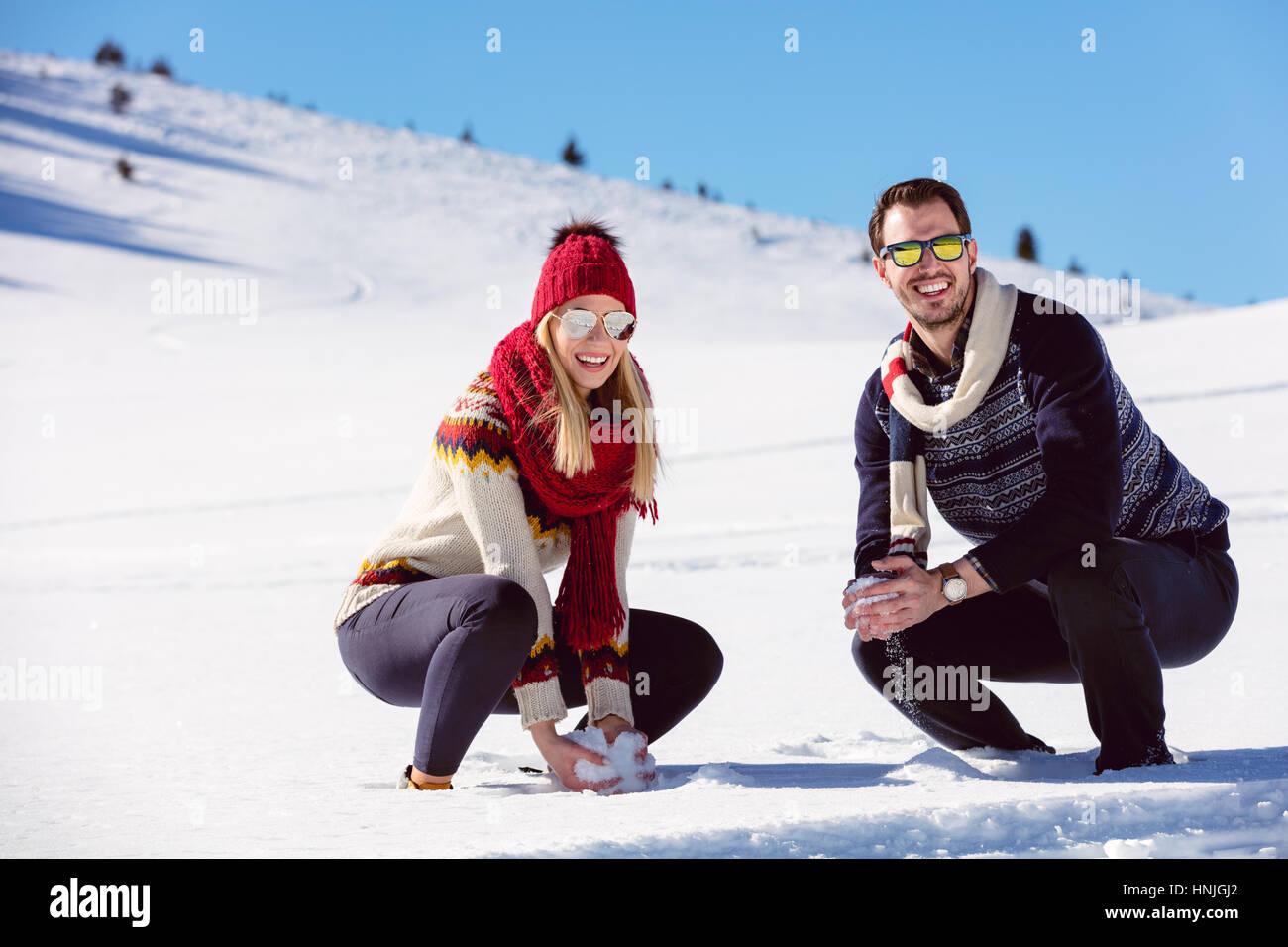 Schneeballschlacht. Winter-Paare, die Spaß im Schnee im Freien spielen. Junge fröhliche multiethnische Stockbild