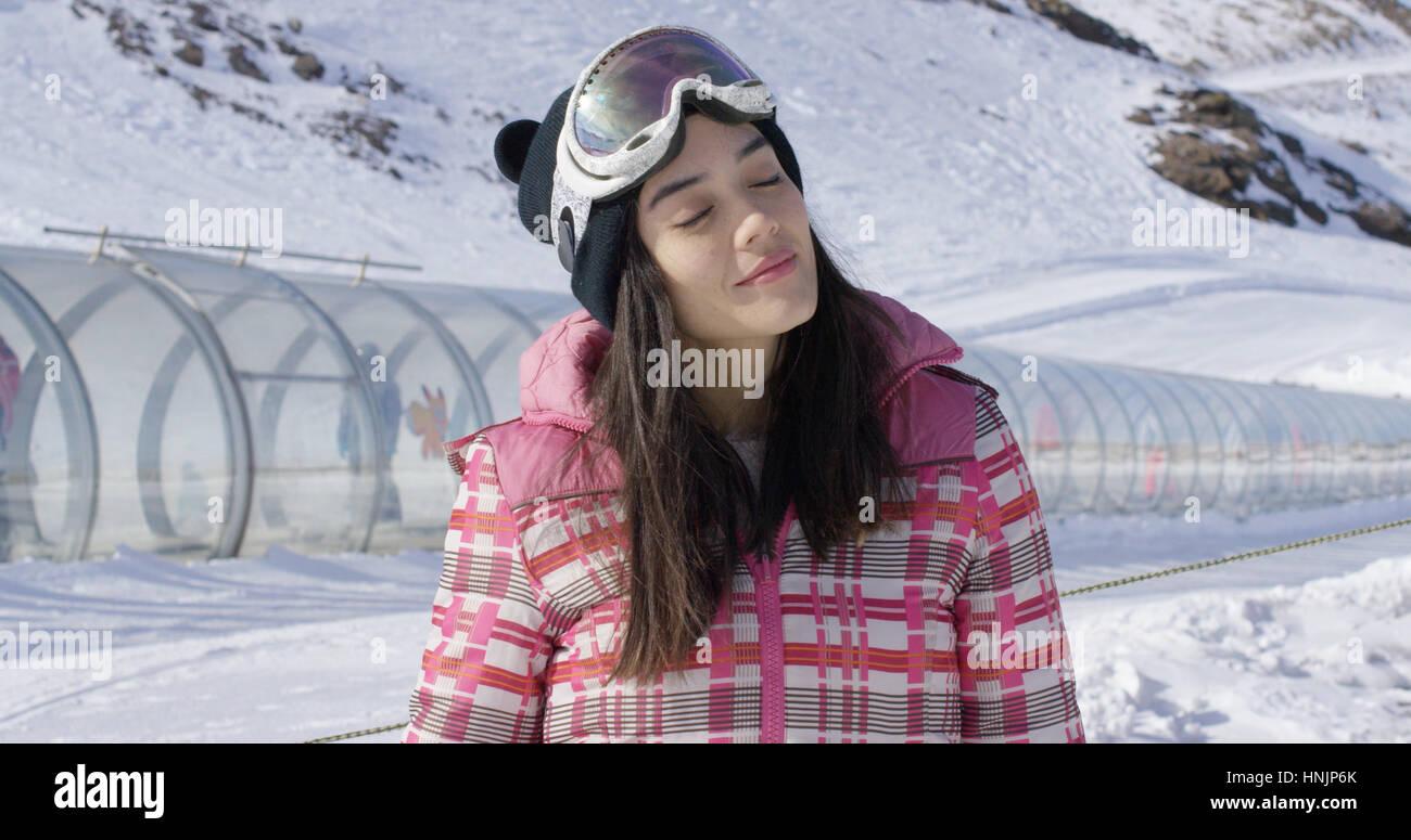 Oberkörper der jungen Frau mit Augen geschlossen im Winter entspannen Sie sich auf der Skipiste Stockbild