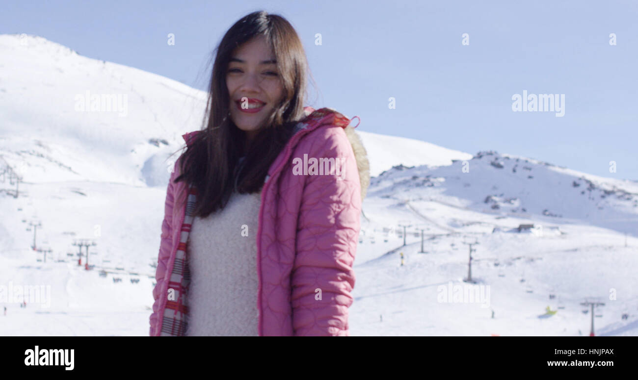 Oberkörper Porträt lächelnder junge Asiatin auf Schnee bedeckt Ski Resort Berghang. Sie lächelt Stockbild