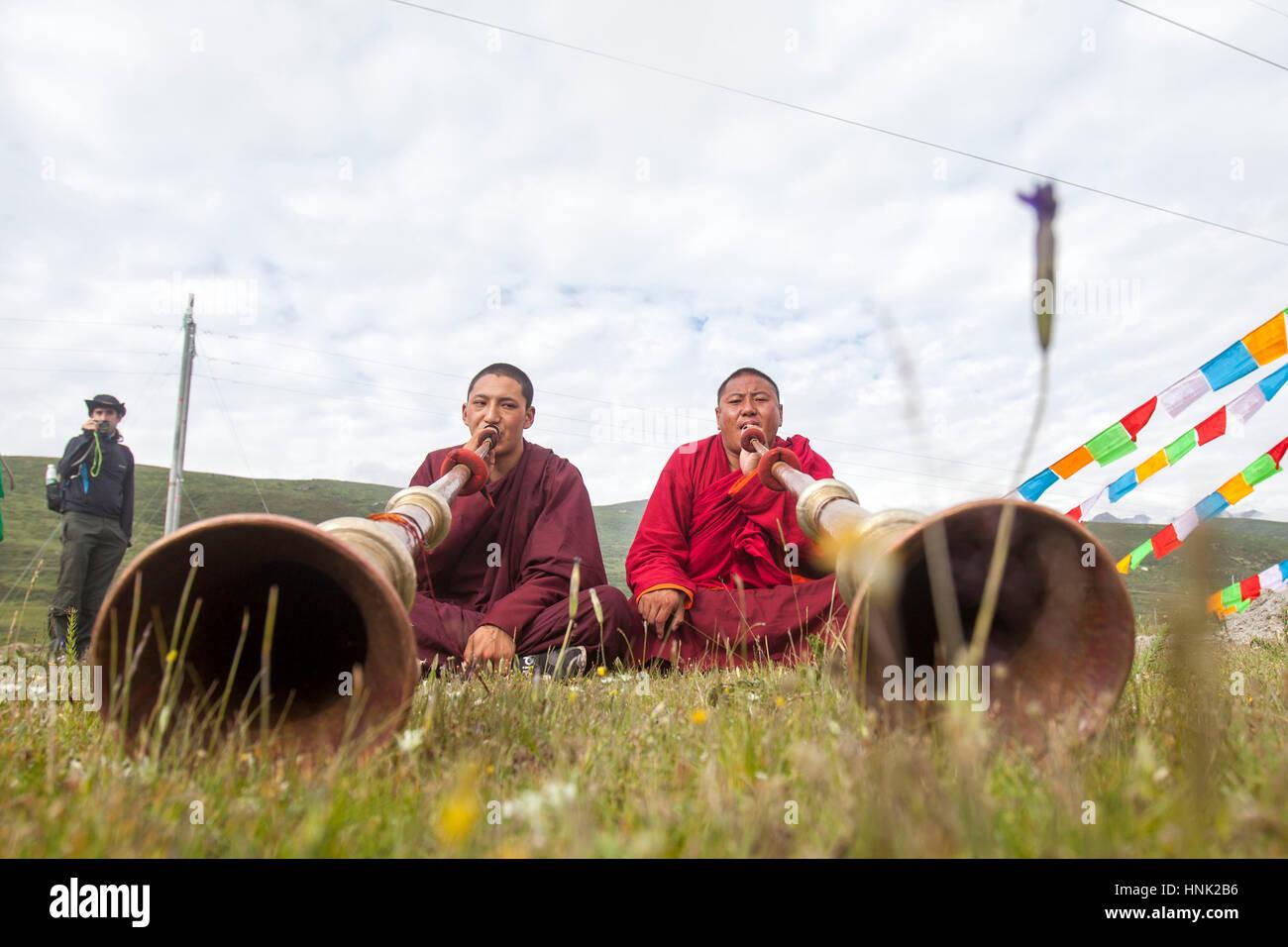 Tibetisch-buddhistische Mönche spielen traditionelle Instrumente um die Reiter vor dem Rennen auf dem Manigango Stockbild