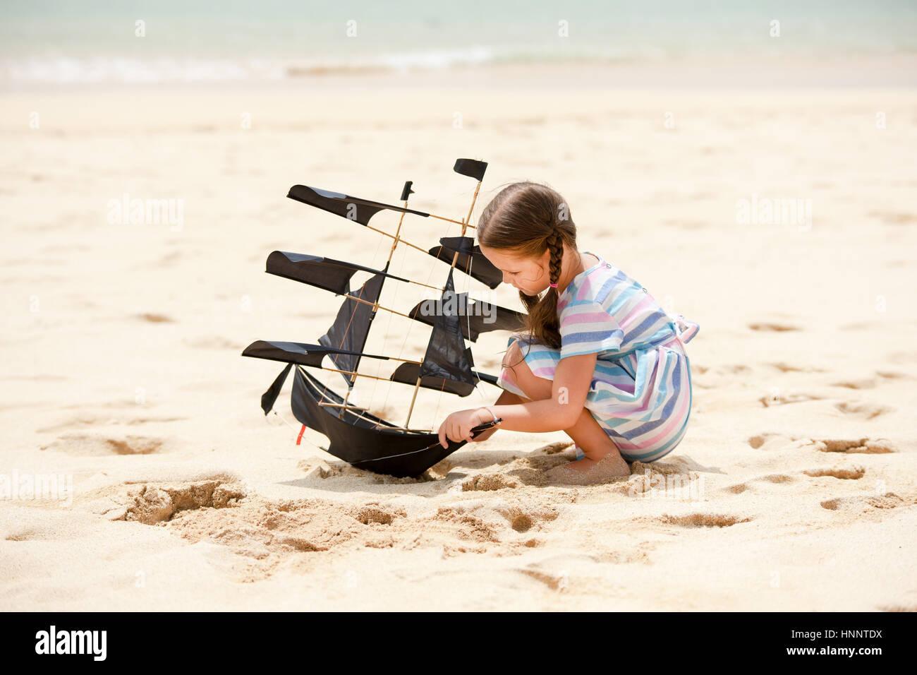Niedliche kleine Mädchen spielen am Strand Drachen Schiff. Kind Sommer-Familienurlaub am Meer genießen. Stockbild