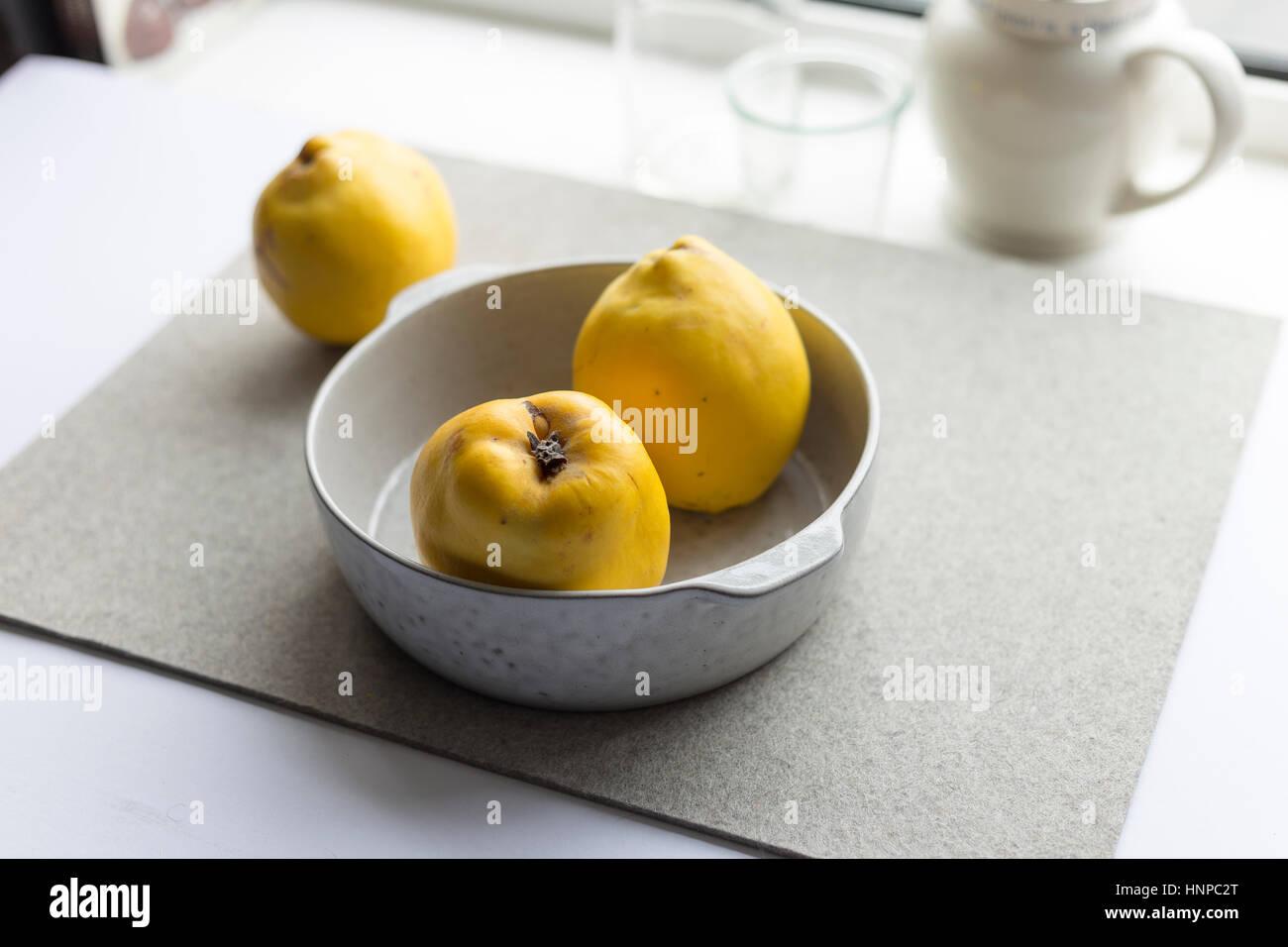 Schüssel mit Quitten auf Tisch Stockbild