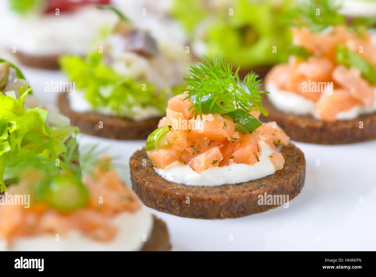 Lecker Fisch Fingerfood mit geräuchertem Lachs Tartar auf Meerrettich, Forellen-Mousse mit Preiselbeeren und Stockbild