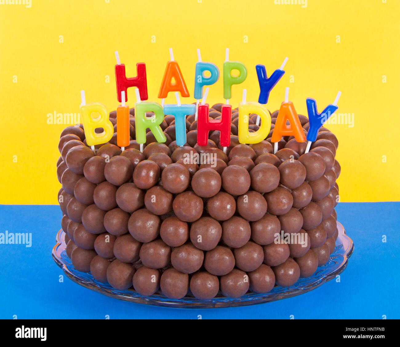 Whopper einer Schokolade Kuchen mit Süßigkeiten Malz Kugeln und Happy Birthday Kerzen dekoriert. Blaue Stockbild