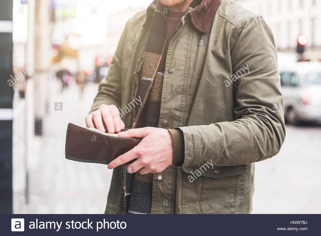 Mann überprüfen Brieftasche vor Geschäft, London, UK Stockbild