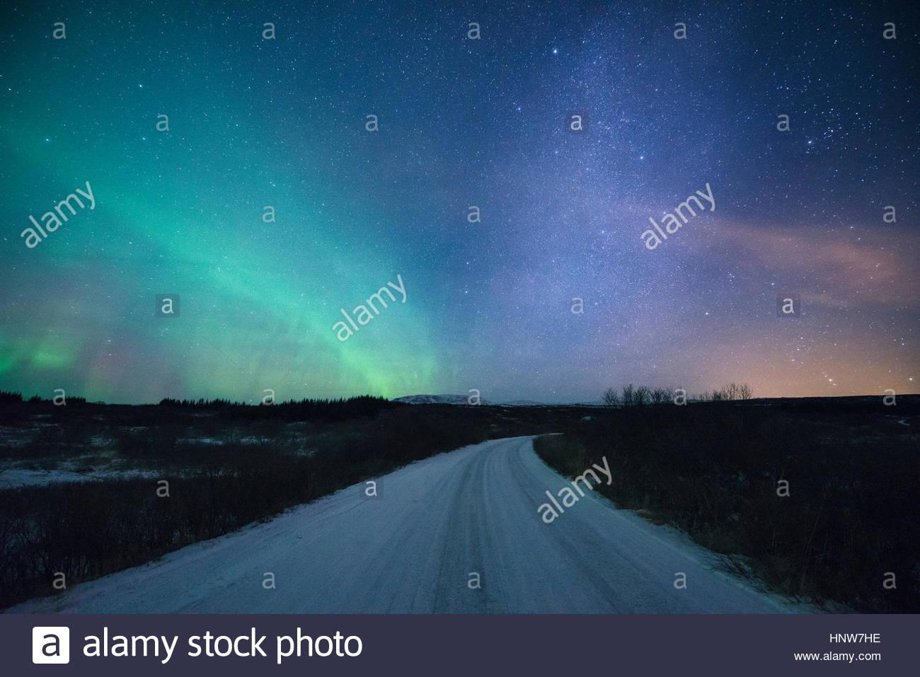 Straße unter Nordlicht in der Nacht, Thingvellir, Island Stockbild