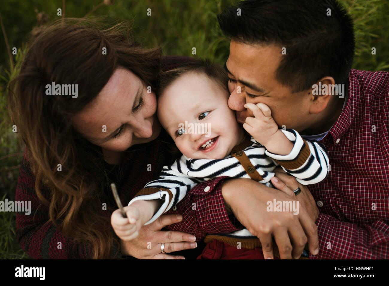Mutter und Vater umarmt lächelndes Baby boy Stockbild