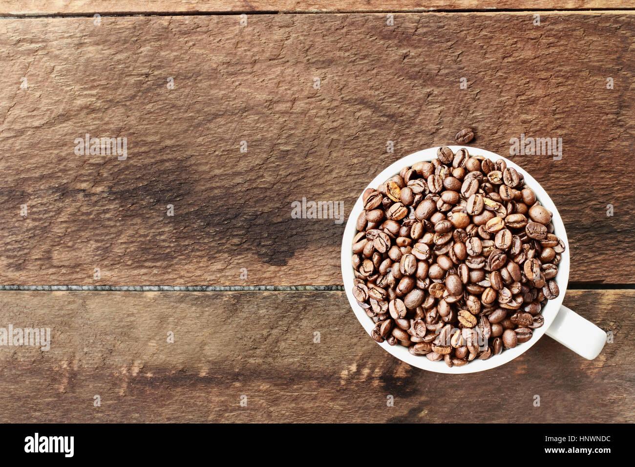 Overhead Schuss einer weißen Tasse gefüllt mit ganz frischen Kaffeebohnen über eine hölzerne Stockbild