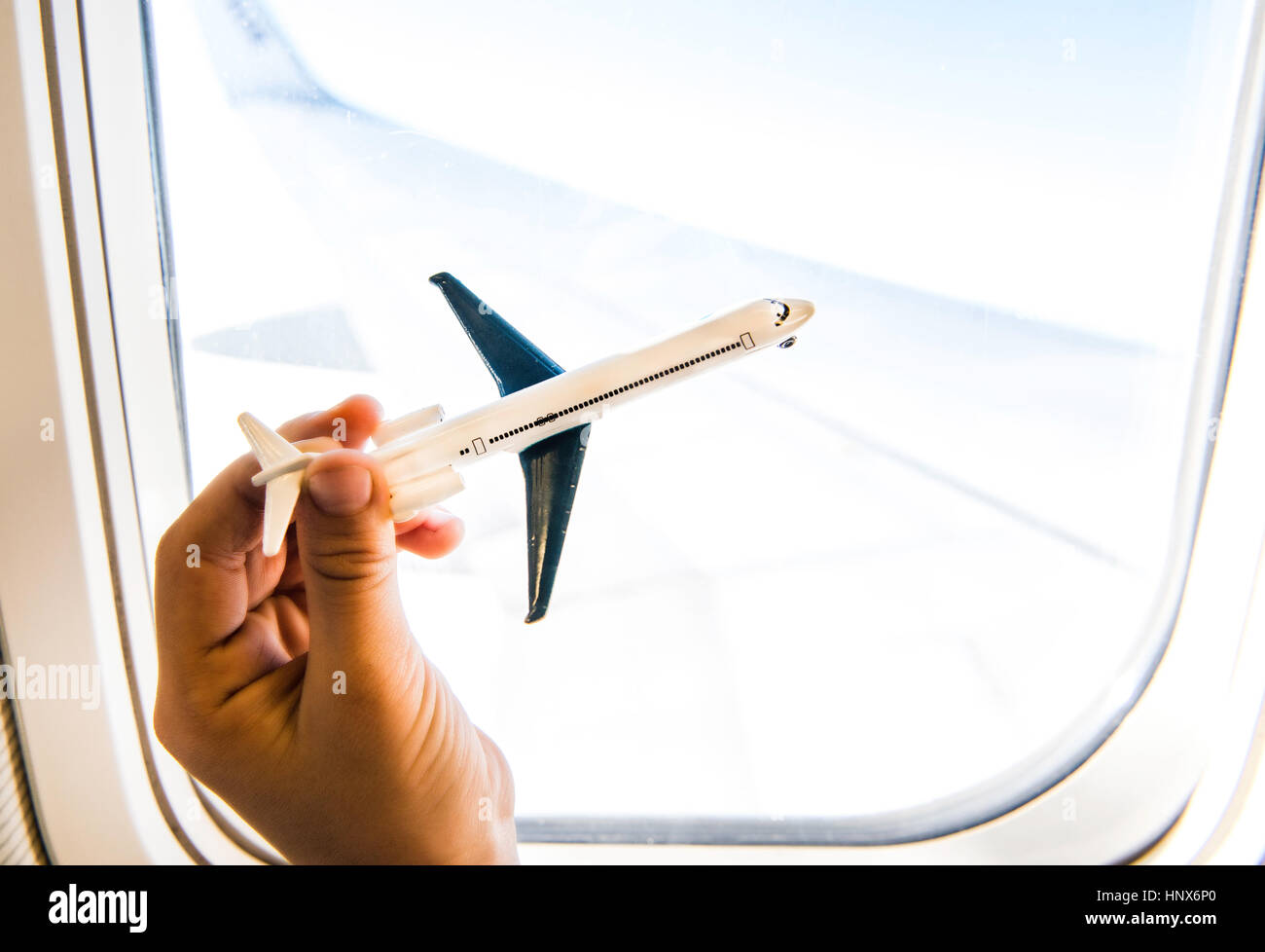 Hand des jungen spielen mit Spielzeugflugzeug im Flugzeugfenster Stockbild