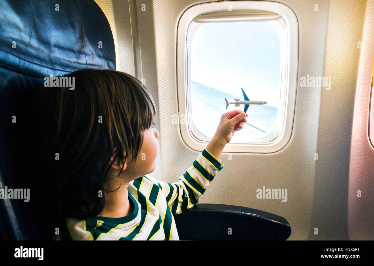 Jungen spielen mit Spielzeugflugzeug im Flugzeugfenster Stockbild