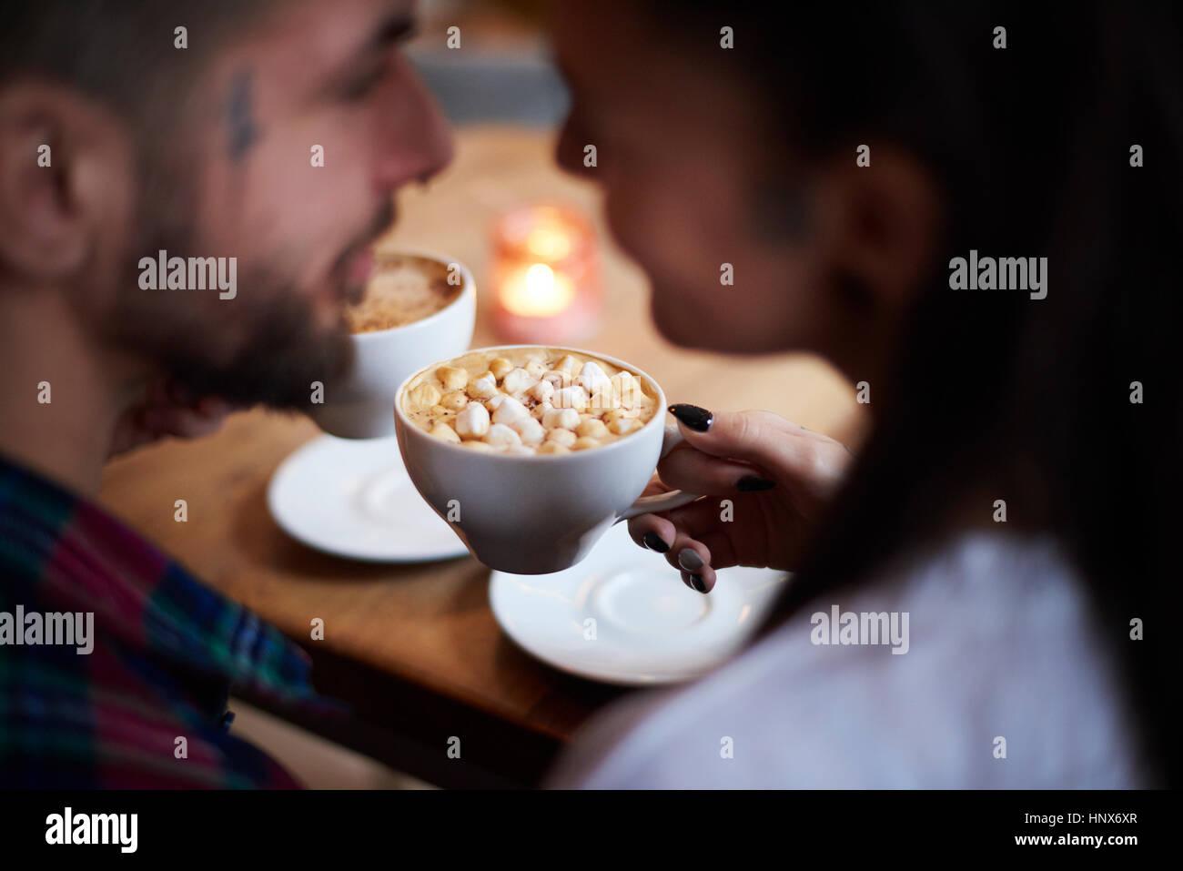 Paar im Café lächelnd von Angesicht zu Angesicht Stockfoto