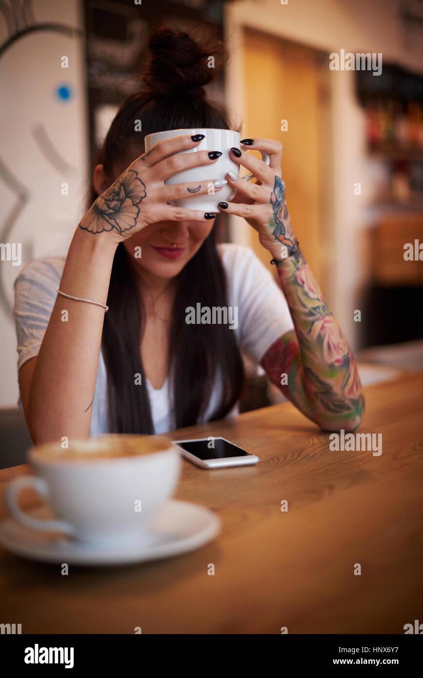 Tätowierte Frau halten Tasse blickte auf smartphone Stockbild