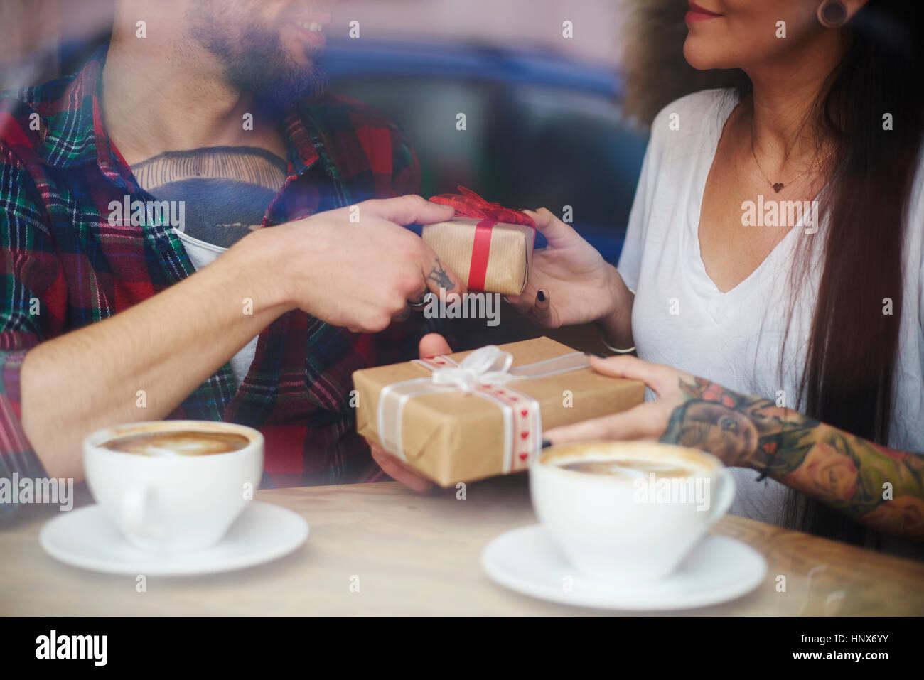 Blick durch die Fenster des Paares im Coffee-Shop, Austausch von Geschenken Stockbild