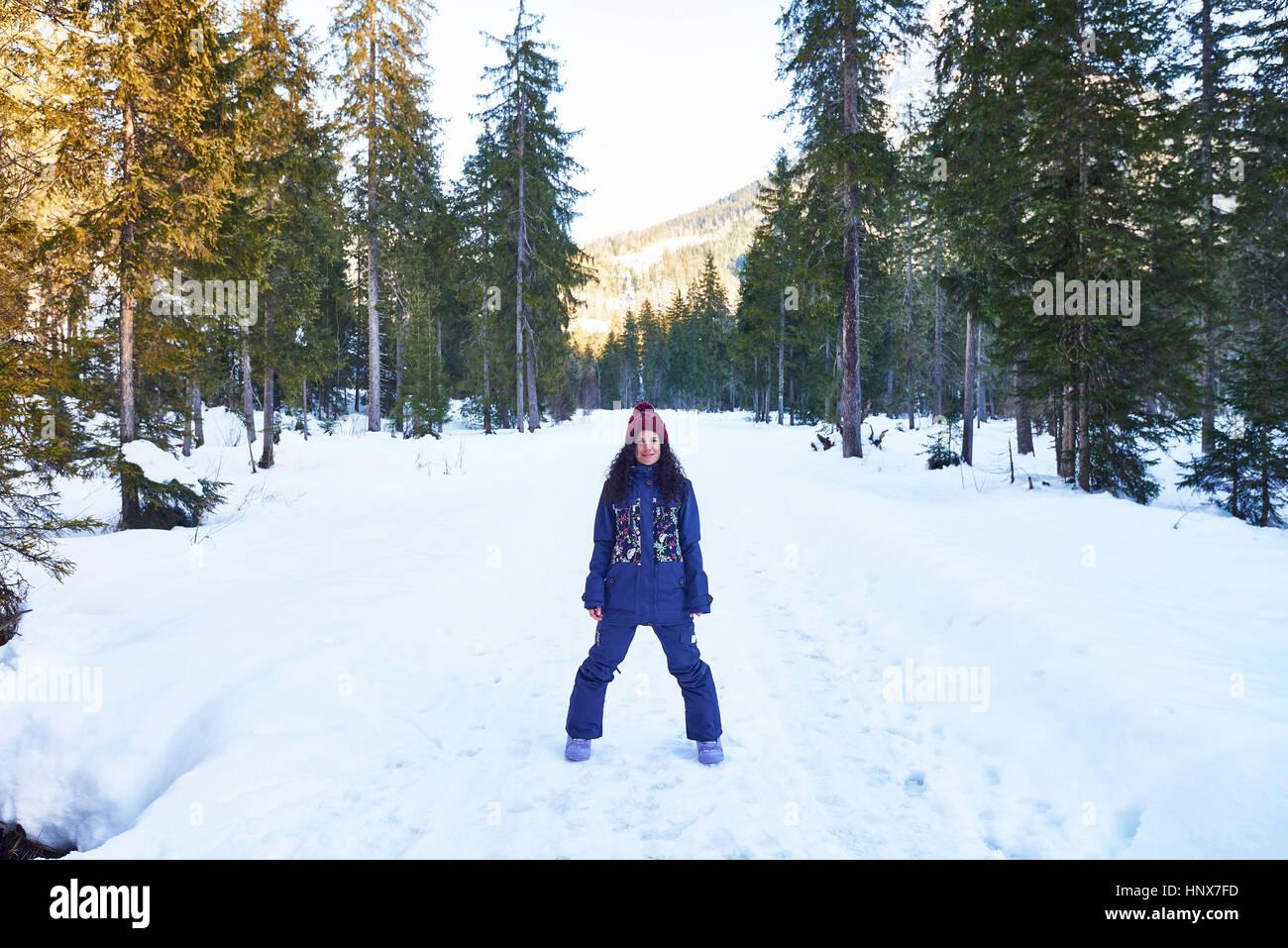 Porträt der Frau im stricken Hut und Winterkleidung im verschneiten Wald, Österreich Stockbild