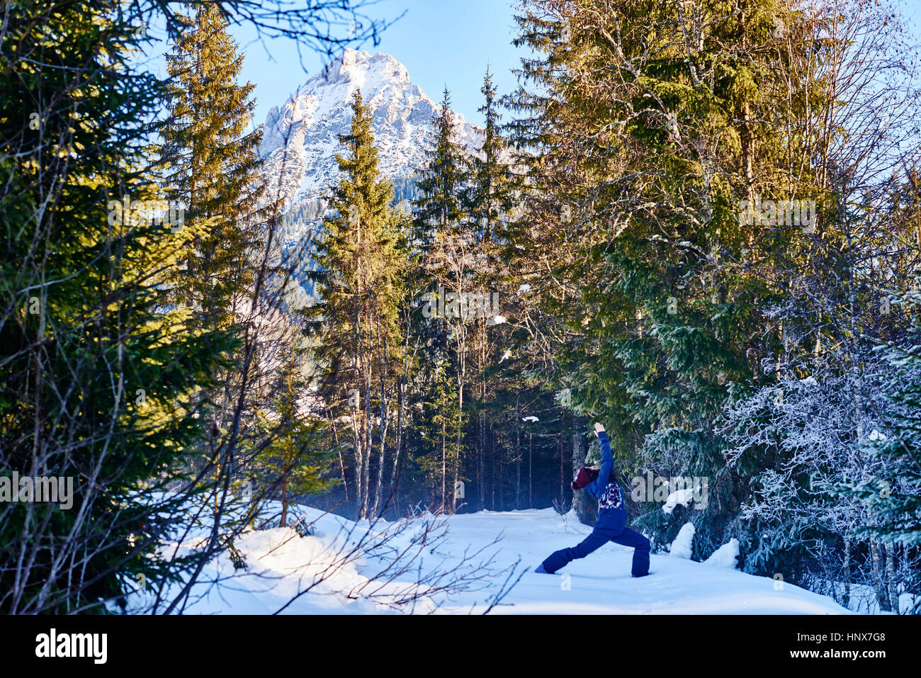 Frau in Winterkleidung üben Krieger Yoga-Pose im verschneiten Wald, Österreich Stockbild