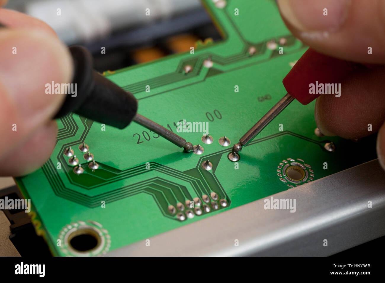 Techniker Prüfungen Kontakt Punkte auf der Platine mit einem Voltmeter (Elektronik Reparatur) - Usa Stockbild