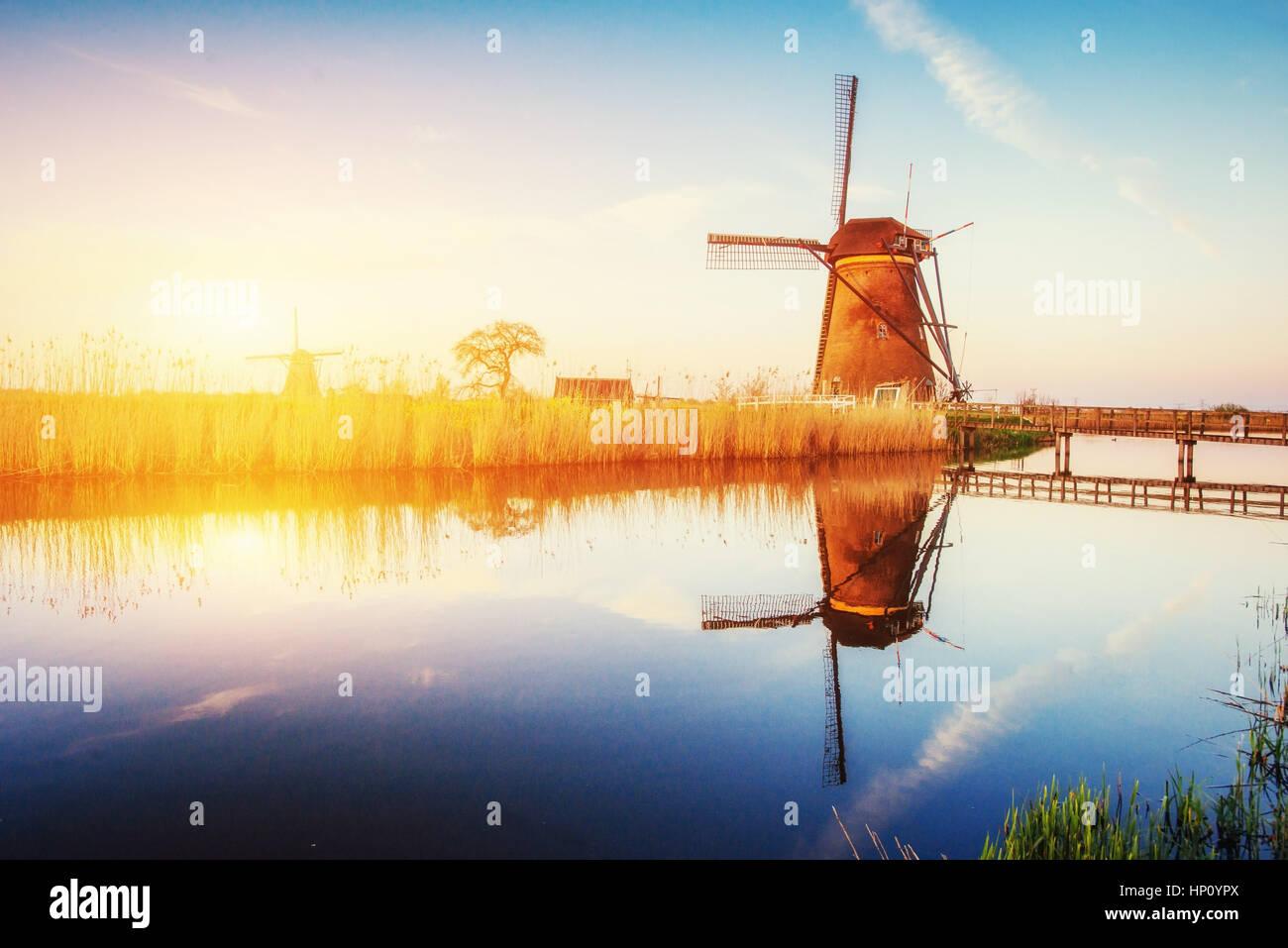Holländische Mühle bei Sonnenuntergang aus dem Kanal in Rotterdam. Holland Stockbild