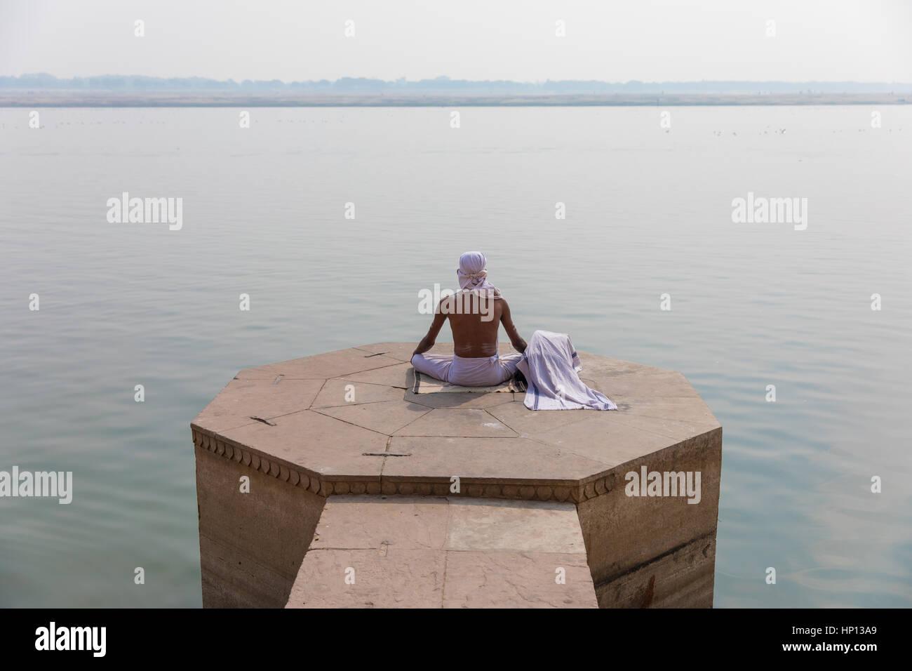 Ein Mann meditiert über den Ganges in Varanasi, eine der heiligsten Städte Indiens. Varanasi ist ein beliebtes Stockbild