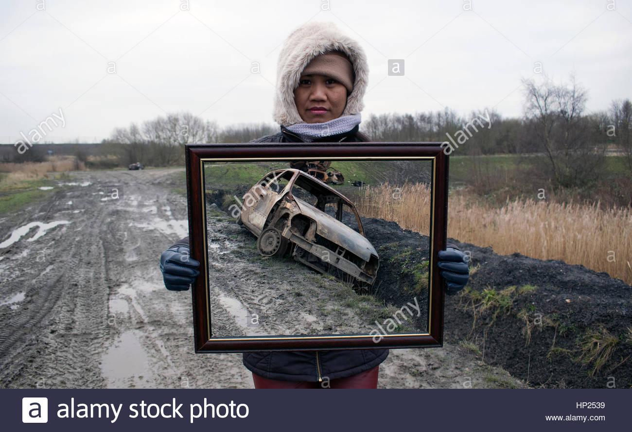 Asiatische Frau mit Bilderrahmen mit gestohlenen & ausgebrannte Auto ...