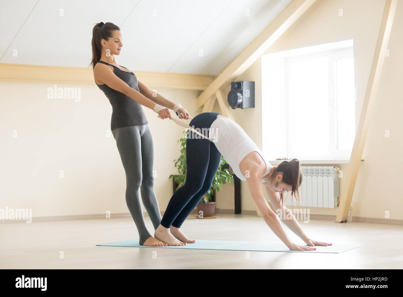 Schöne weibliche Yogi Lehrer unterstützen junge Frau im Yoga clas Stockbild