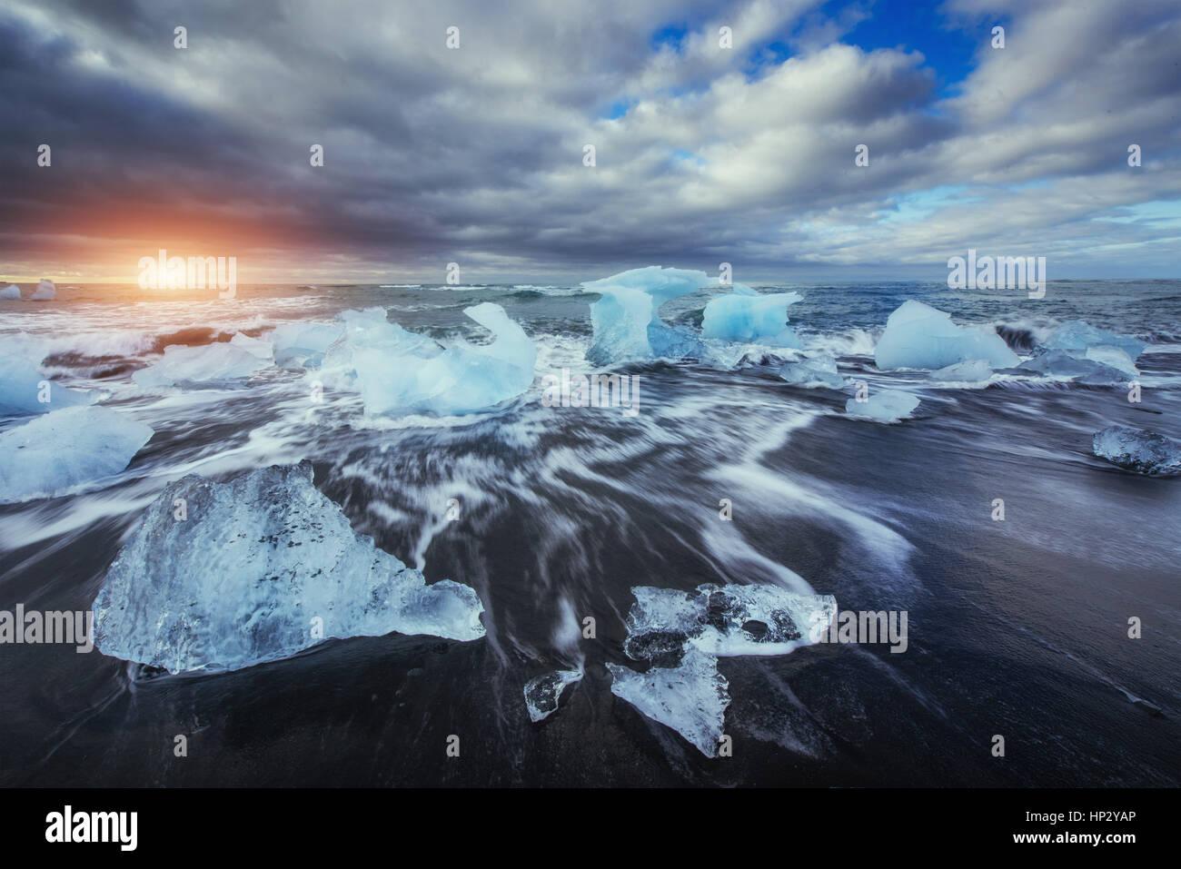 Jökulsárlón Gletscher Lagune fantastischen Sonnenuntergang am schwarzen Strand, Stockbild