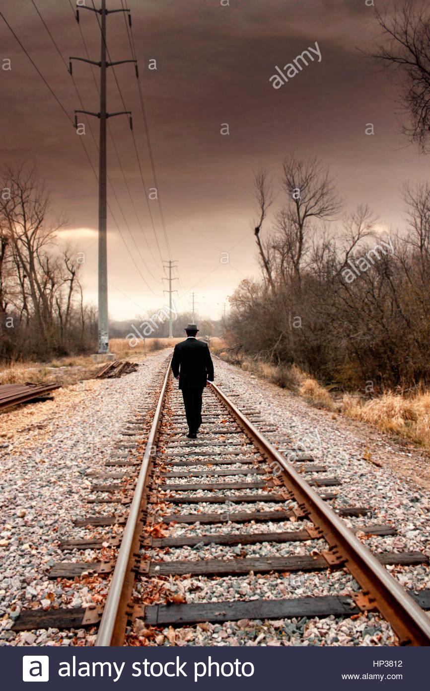 Gut gekleidete junge Mann zu Fuß entfernt, auf Schienen Stockbild