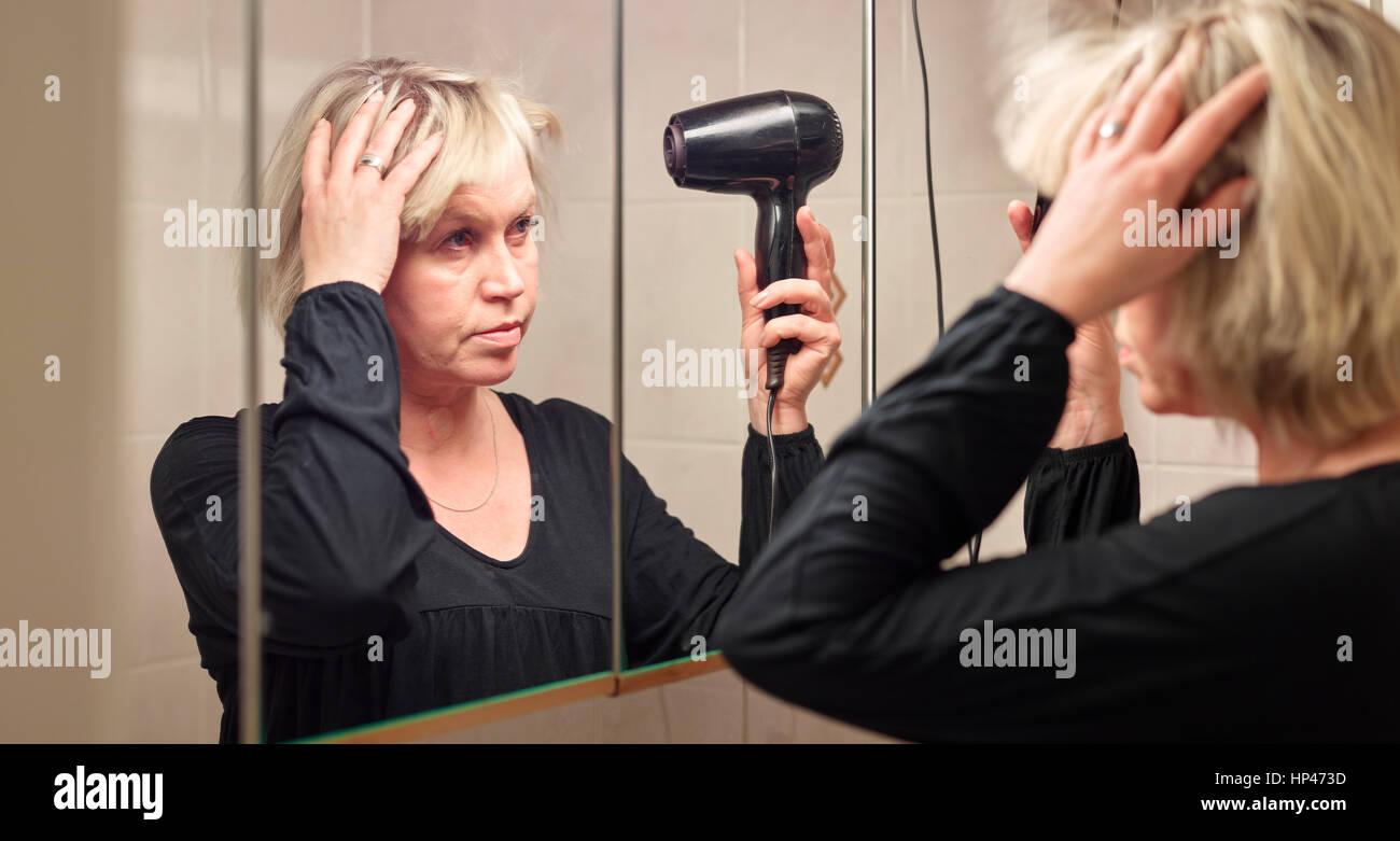 Reife Frau verwendet einen Fön im Bad Stockbild