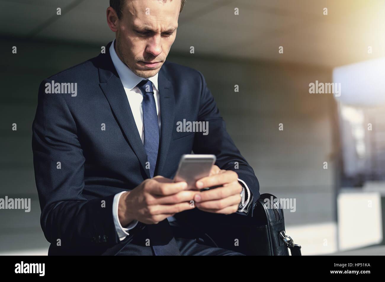 Zuversichtlich gut aussehender Geschäftsmann mit seinem Telefon. Horizontale drinnen geschossen Stockbild