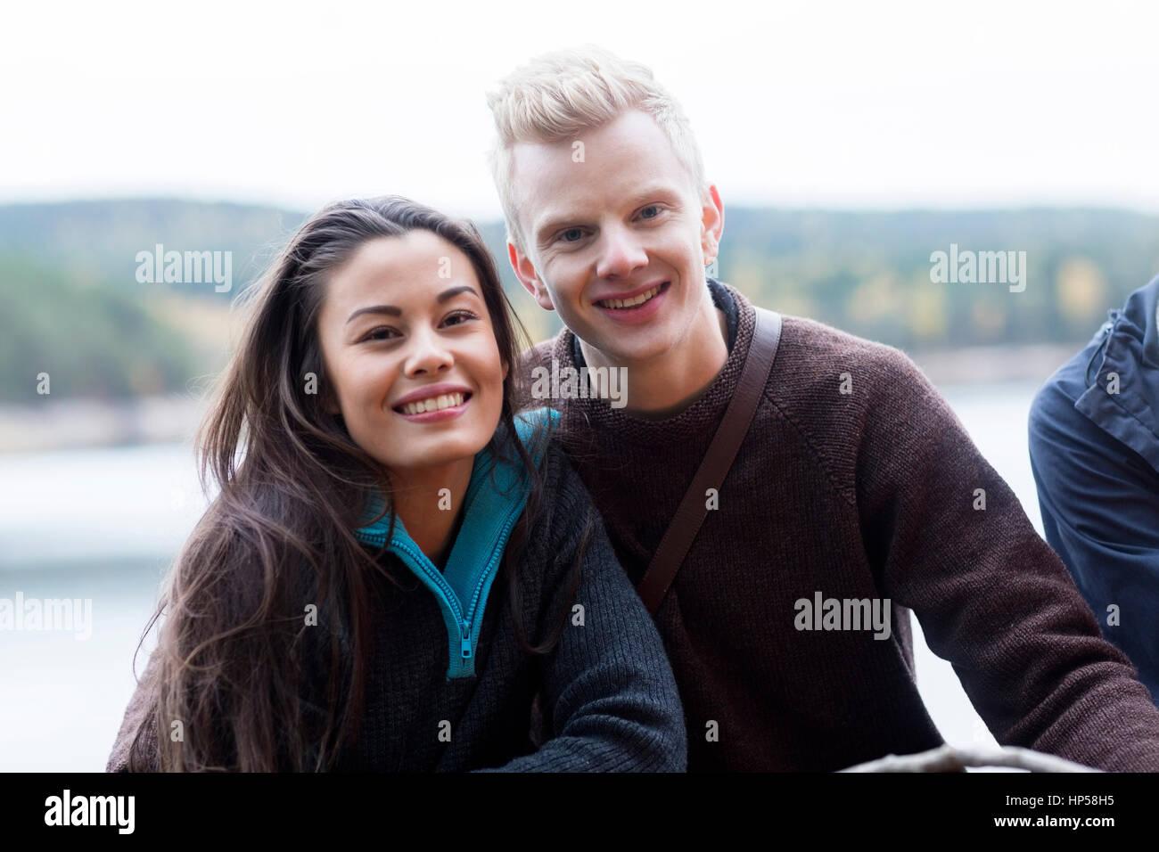 Lächelnd multiethnischen Ehepaar am See Camping Stockbild